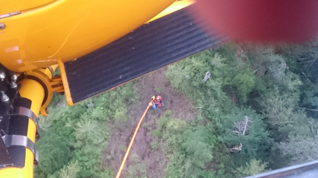 Subject and two rescuers being picked up